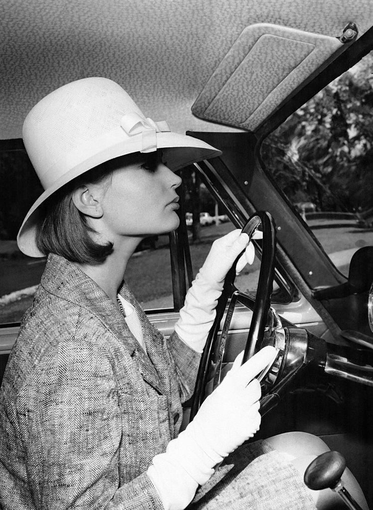 <p>A woman sporting a stylish skirt suit with driving gloves and a bow-detailed hat.</p>