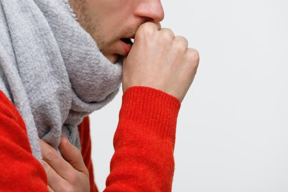 unhealthy man in orange sweater suffering with pulmonary cough