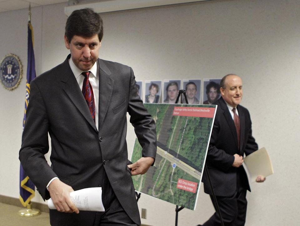 U.S. Attorney Steven Dettelbach, left, and FBI special agent in charge Stephen Anthony walk past a map showing the location of a bridge on Ohio Rt. 82 south of Cleveland Tuesday, May 1, 2012. Five men, pictured on the wall behind the map, have been arrested for conspiring to blow up the high level bridge over the Cuyahoga River valley. (AP Photo/Mark Duncan)