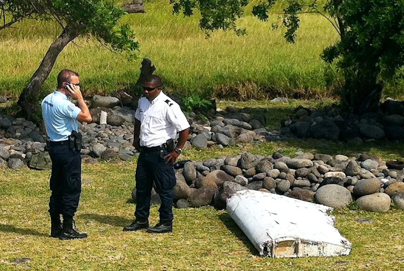 Polcie officers stand next to a piece of debris from an unidentified aircraft found in the coastal area of Saint-Andre on the Indian Ocean island of La Reunion on July 29, 2015 (AFP Photo/Yannick Pitou)