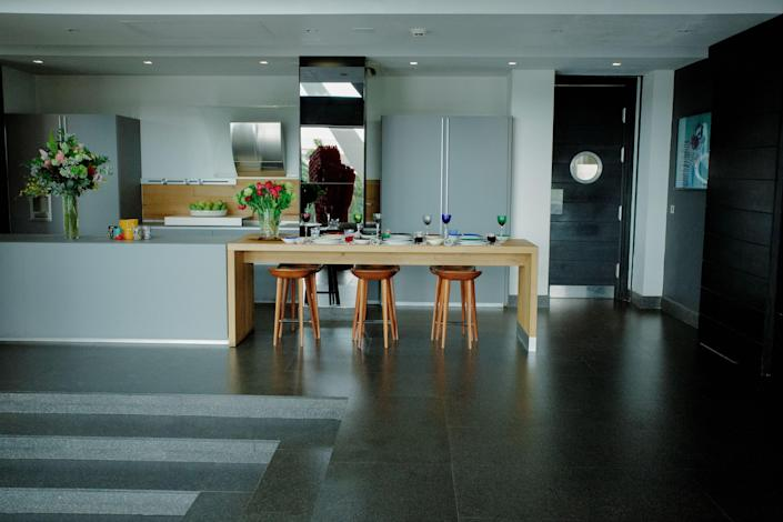 The kitchen is outfitted with Gaggenau appliances. Counter stools by Bassamfellows.
