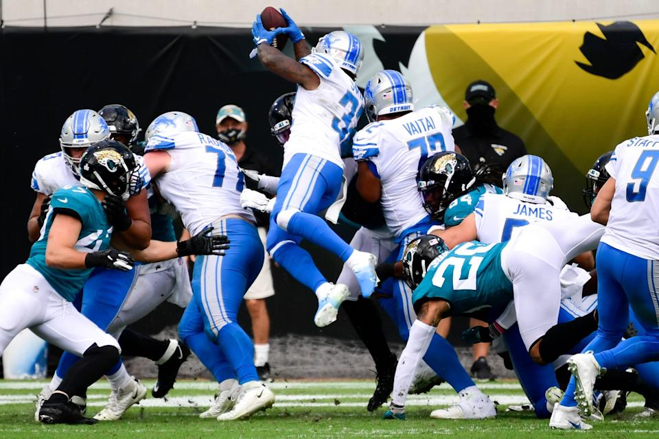 Detroit Lions running back D'Andre Swift leaps over the pile for a touchdown against the Jacksonville Jaguars during the first half at TIAA Bank Field, Oct. 18, 2020.