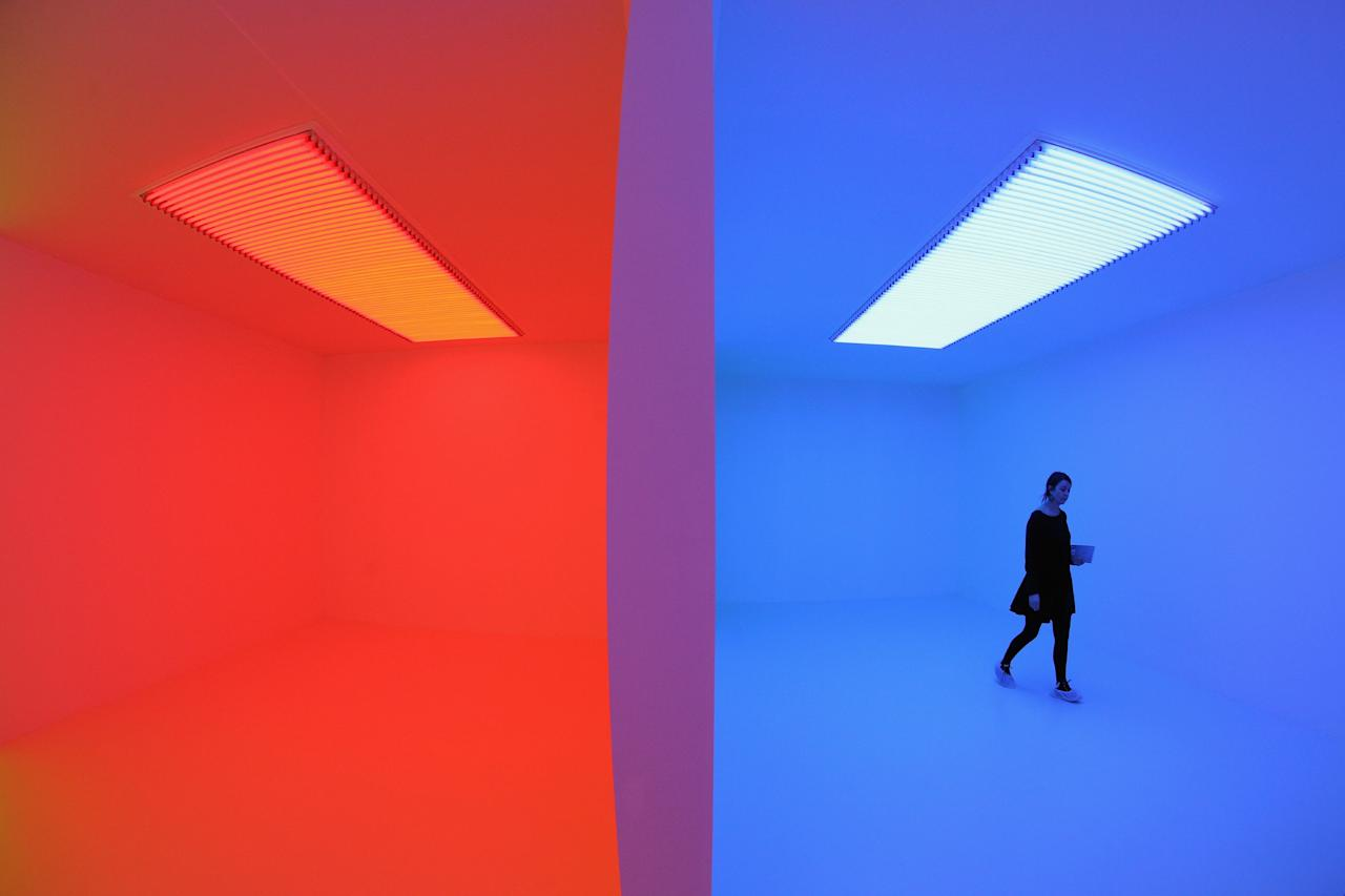 LONDON, ENGLAND - JANUARY 29:  A woman admires an art installation by Carlos Cruz-Diez entitled 'Chromosaturation' which features in the Hayward Gallery's exhibition 'Light Show' on January 29, 2013 in London, England. 'Light Show' features 25 illuminated installations and sculptures by major international artists from the 1960s to the present day. The show opens to the general public on January 30, 2013 and runs until April 28, 2013.  (Photo by Oli Scarff/Getty Images)