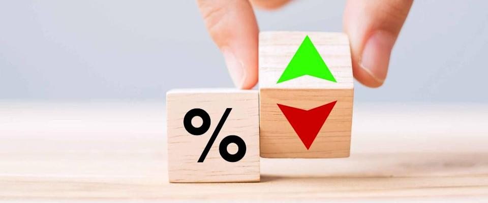 businessman Hand change wooden cube block with percentage up and down arrow symbol icon.  Interest rate, stocks, financial, ranking, mortgage rates and loss reduction concept