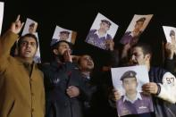 Relatives of Islamic State captive Jordanian pilot Muath al-Kasaesbeh hold up his pictures as they chant slogans demanding that the Jordanian government negotiate with Islamic state and for the release of Kasaesbeh, in front of the prime minister's building in Amman, January 27, 2015. REUTERS/Muhammad Hamed