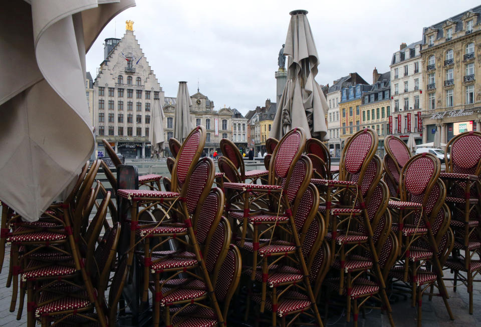 Chairs are stacked up outside an empty restaurant in the center of Lille, northern France, Sunday March 15, 2020. French Prime Minister Edouard Philippe announced that France is shutting down all restaurants, cafes, cinemas and non-essential retail shops, starting Sunday, to combat the accelerated spread of the virus in the country. For most people, the new coronavirus causes only mild or moderate symptoms. For some it can cause more severe illness. (AP Photo/Michel Spingler)
