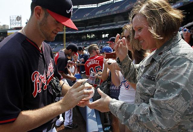 Atlanta Braves pitcher Alex Wood (40) signs a baseball for Major Patricia Hood, of the Georgia Air National Guards 116th Medical Group, before a baseball game against the Boston Red Sox on Monday, May 26, 2014, in Atlanta, Ga. (AP Photo/Butch Dill)
