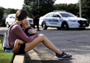 Carly McWatters holds her son at Collierville Town Hall on Friday, Sept. 24, 2021, in Collierville, Tenn., to pay their respects to the victims of the Kroger shooting the day before. (Patrick Lantrip/Daily Memphian via AP)