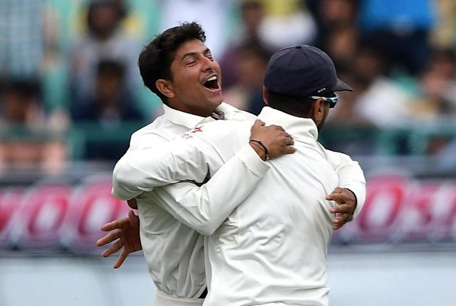 India's Kuldeep Yadav (L) celebrates the wicket of Australia's Peter Handscomb with teammate Murali Vijay during the fourth Test at The Himachal Pradesh Cricket Association Stadium in Dharamsala on March 25, 2017 (AFP Photo/Prakash SINGH)