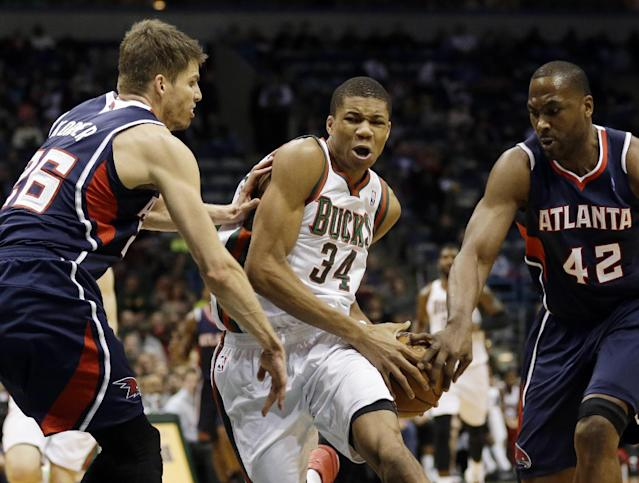 Milwaukee Bucks' Giannis Antetokounmpo (34) drives against the Atlanta Hawks' Kyle Korver, left, and Elton Brand (42) during the second half of an NBA basketball game Saturday, Jan. 25, 2014, in Milwaukee. (AP Photo/Jeffrey Phelps)