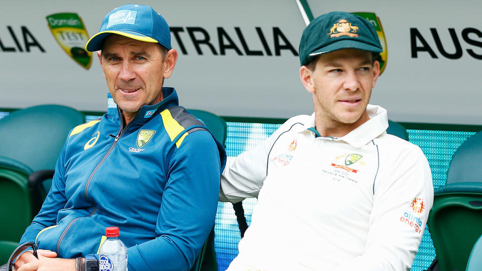 Australia head coach Justin Langer (L) looks forward and sits with Tim Paine as he reaches out his arm.