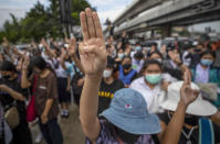 Pro-democracy activists flash three-fingered salute during a demonstration at Kaset intersection, suburbs of Bangkok, Thailand, Monday, Oct. 19, 2020. Thailand's embattled Prime Minister Prayuth Chan-ocha said Monday that there were no plans to extend a state of emergency outside the capital, even as student-led protests calling for him to leave office spread around the country. (AP Photo/Sakchai Lalit)