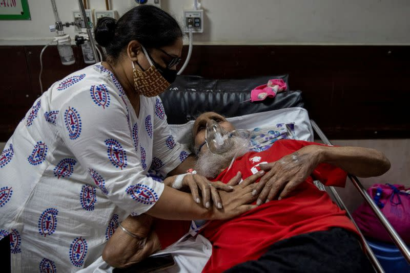 A man suffering from the coronavirus disease (COVID-19) is comforted by his daughter as he receives treatment inside the casualty ward at a hospital in New Delhi