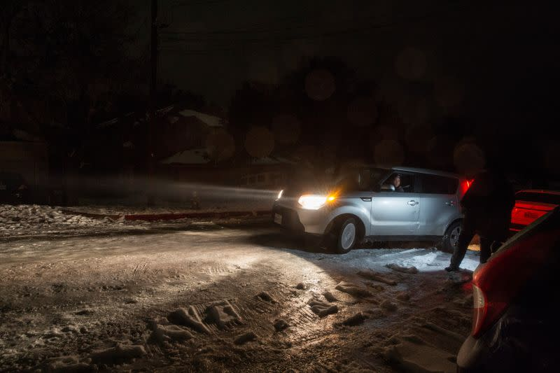 A woman attempts to move her car as she gets stuck on ice following winter weather in San Marcos