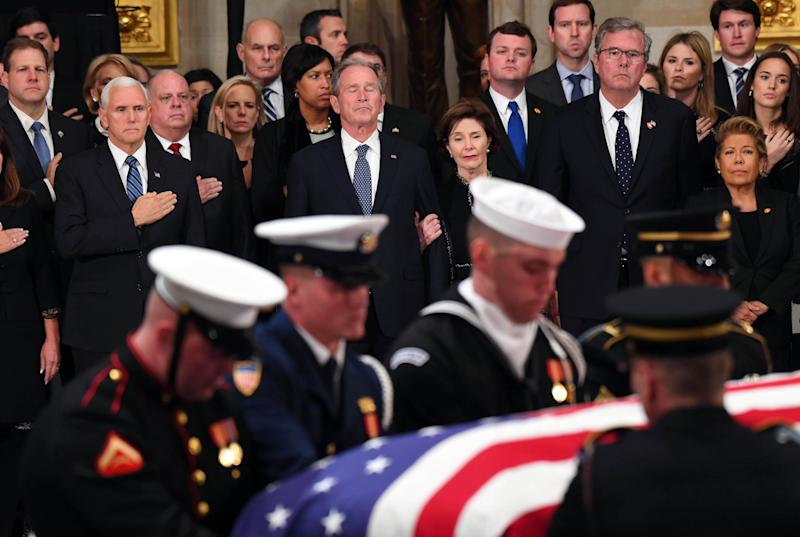 President George W. Bush and his wife Laura Bush look on as President George H.W. Bush arrives to lie in state at the U.S. Capitol Rotunda on Dec. 3, 2018.