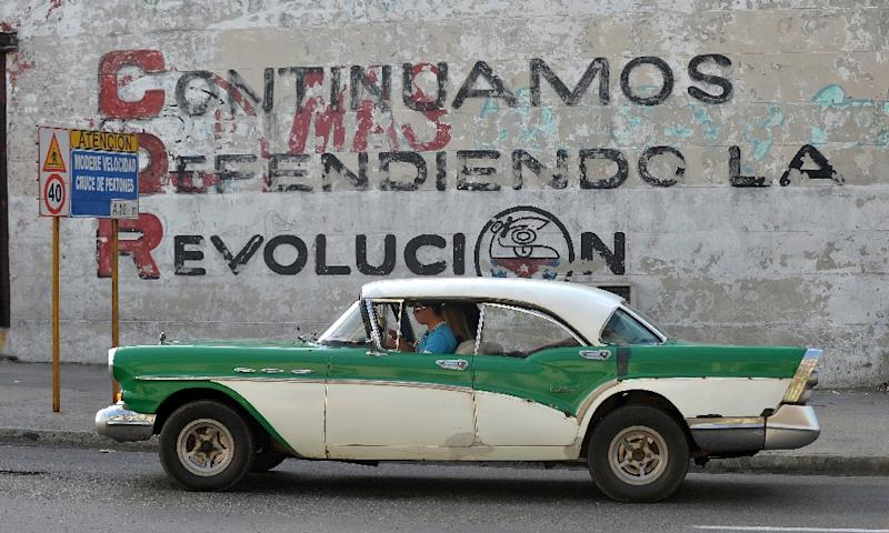 """A car drives past a wall in Havana reading """"We Continue Defending the Revolution,"""" but new leadership is expected to embody both continuity and change (AFP Photo/Yamil LAGE)"""