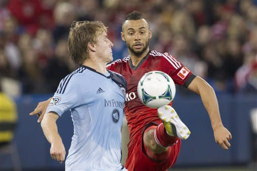Toronto FC's John Bostock, right, battles for the ball with Sporting Kansas City Seth Sinovic during ssecond half MLS soccer action in Toronto on Saturday, March 9, 2013. (AP Photo/The Canadian Press, Chris Young)