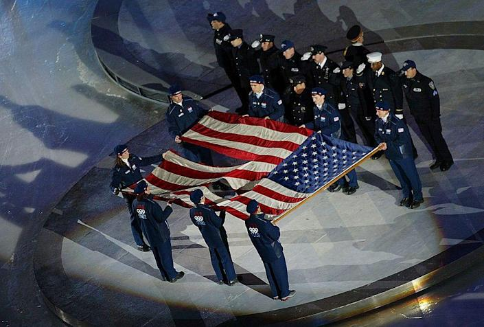 <p>An American flag from the World Trade Center is carried and raised by an honor guard of athletes, police officers, and firefighters.</p>