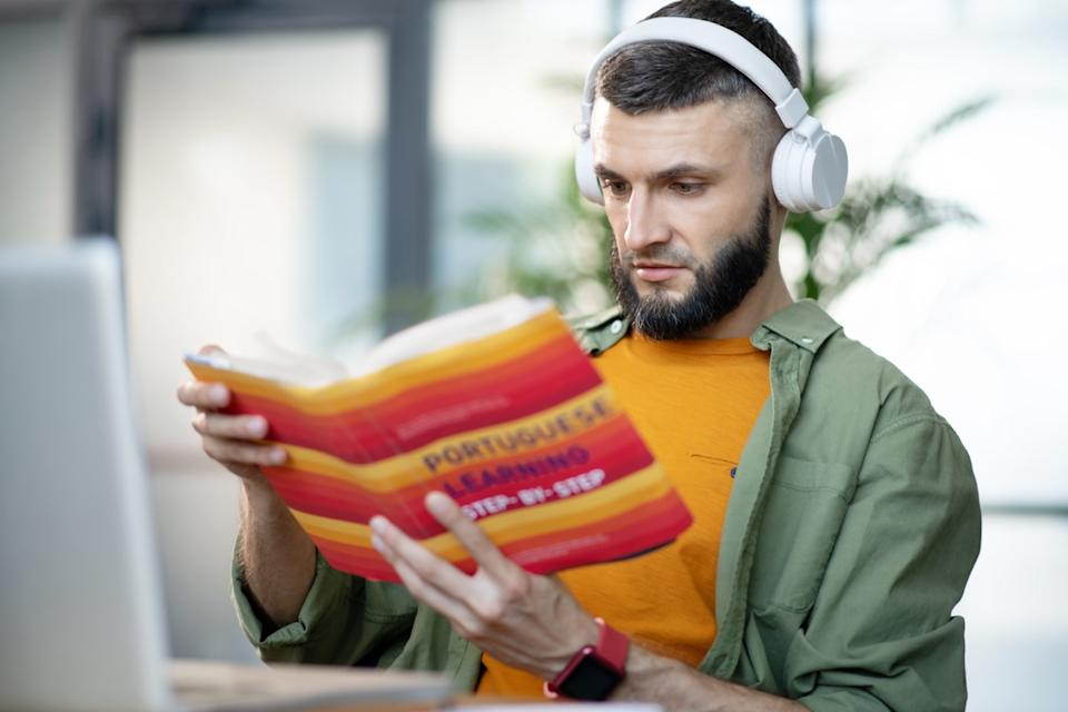 man reading a portuguese language book to learn the language