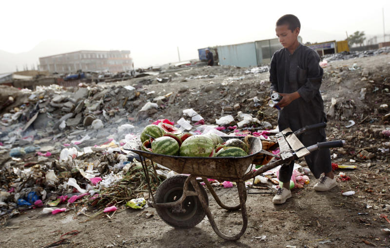An Afghan boy loads a wheelbarrow with sellable materials that he recovered from a garbage dump in Kabul, Afghanistan, Monday, June 27, 2011.  The U.N. World Food Program (WFP) announced Monday it will cut food assistance to more than 3 million Afghans in about half the country's 34 provinces because of a shortage of money from donor nations.The program will focus food assistance on helping the most needy Afghans, especially women and children, said Bradley Guerrant, the agency's deputy country director.(AP Photo/Gemunu Amarasinghe)