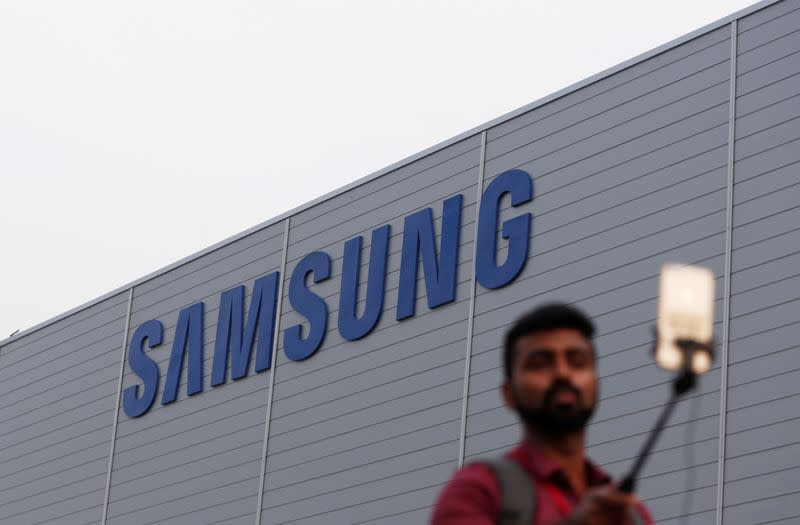 A journalist uses a mobile phone as he works outside the Samsung Electronics smartphone manufacturing facility in Noida