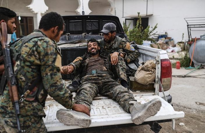 A heavily wounded member of the Syrian Democratic Forces smiles as he arrives at a medical centre on the eastern frontline of the battle to retake the one-time Islamic State bastion of Raqa (AFP Photo/BULENT KILIC)