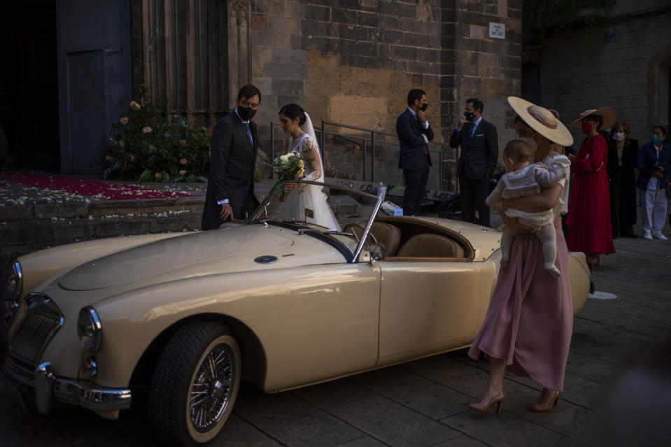 Newlyweds and guests leave the church during a wedding in Barcelona, Spain, Saturday Oct. 17, 2020. (AP Photo/Emilio Morenatti)