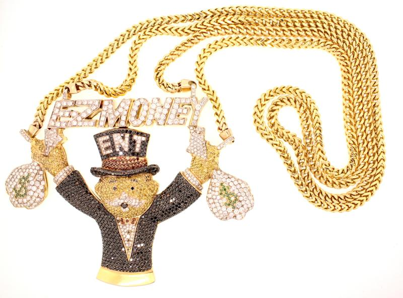 This image provided by Gaston & Sheehan Auctioneers shows a necklace featuring a banker is one of the items being auctioned off Saturday June 1, 2013, in Las Vegas. The auction features precious metals, gems and jewelry confiscated by U.S. Marshals during federal criminal cases. Bidding for the necklace begins at $13,250. Buyers can preview the gold and silver bullion, coins, jewelry and watches from federal crime cases Friday at the Las Vegas Convention Center.(AP Photo/Gaston & Sheehan Auctioneers)