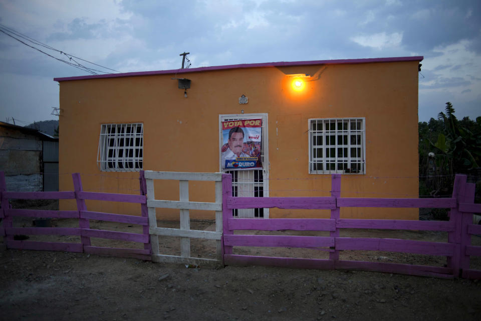 """In this April 8, 2013 photo, a campaign poster featuring the ruling party presidential candidate, acting President Nicolas Maduro, hangs from a security door at a home in Tacarigua, Venezuela. Outside Venezuela's capital, power outages, food shortages and unfinished projects abound; important factors heading into Sunday's election to replace Chavez, who died last month after a long battle with cancer. An estimated 2 million of Venezuela's country's nearly 30 million people lack permanent homes, and one of Chavez's anti-poverty """"missions"""" builds them. But it's been slow going. The government says it has built 370,500 homes and apartments over the past two years, and more than 3 million people applied for them. (AP Photo/Ramon Espinosa)"""