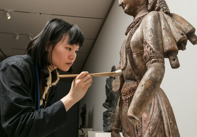 A woman does restoration work on a bronze statue.