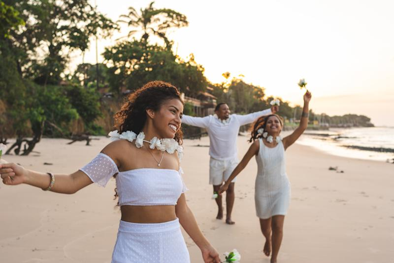Happy friends celebrating reveillon on the beach, running and holding white flowers. They wear white clothes. Group of young people enjoying and partying together. Happiness, togetherness, youth and new year's eve concepts. Paraiso beach, Mosqueiro