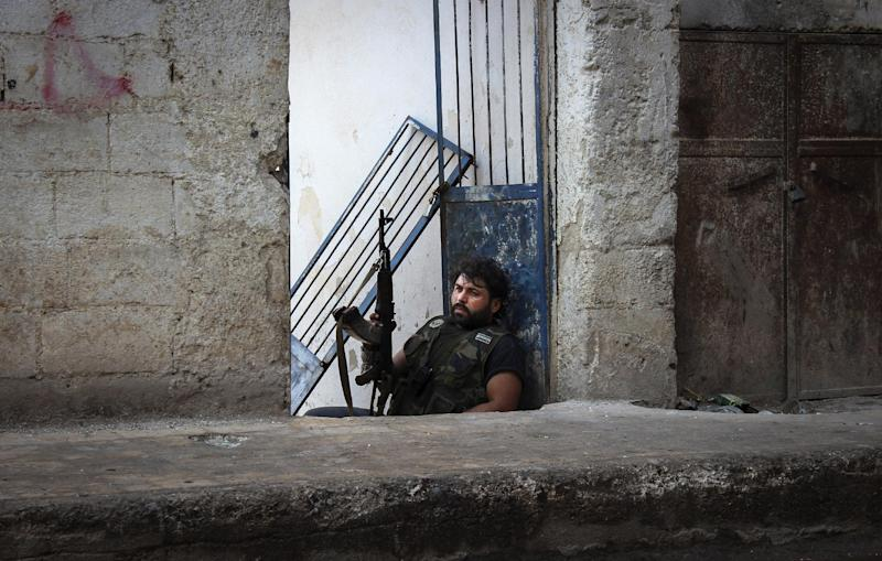 FILE - In thisTuesday, Oct. 30, 2012 file photo, Mustafa, a rebel from the town of Bennish, watches for a sniper firing down a street in the town of Harem, Syria. A dark realization is spreading across north Syria that despite 20 months of violence and recent rebel gains, an end to the war to topple President Bashar Assad is nowhere in sight. (AP Photo/Mustafa Karali, File)