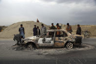 FILE - In this April 9, 2019, file photo, Afghans watch a civilian vehicle burnt after being shot by U.S. forces following an attack near the Bagram Air Base, north of Kabul, Afghanistan. Afghanistan has been at war for more than 40 years, first against the invading Soviet army that killed more than 1 million people, then feuding mujahedin groups in a bitter civil war followed by the repressive Taliban rule and finally the latest war that began after the 2001 U.S.-led coalition invasion that toppled the Taliban government. (AP Photo/Rahmat Gul, File)