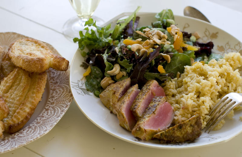 This Nov. 18, 2013 photo shows coconut cashew salad with apricots, seared curry rubbed tuna with mango tahini rice, and tangerine twirls in Concord, N.H. It's a mash-up that draws on the flavors of the Caribbean, Southeast Asia and Europe. (AP Photo/Matthew Mead)