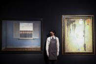 A gallery assistant stands next to artwork titled 'Le Mois des Vendanges' by Rene Magritte and 'Peinture' by Joan Miro, during a photocall at Christie's auction house, in London