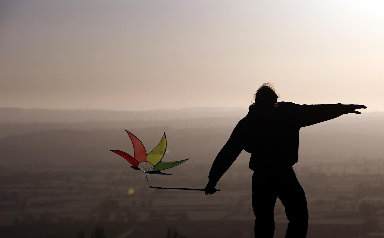 GLASTONBURY, ENGLAND - MAY 01:  A person holds a holds a windmill as people watch the sun rise as they join in a Beltane dawn celebration service in front of St. Michael's Tower on Glastonbury Tor on May 1, 2013 in Glastonbury, England. Although more synonymous with International Workers' Day, or Labour Day, May Day or Beltane is celebrated by druids and pagans as the beginning of summer and the chance to celebrate the coming of the season of warmth and light. Other traditional English May Day rites and celebrations include Morris dancing and the crowning of a May Queen with celebrations involving a Maypole.  (Photo by Matt Cardy/Getty Images)