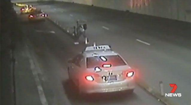 A cyclist seen trying to cross the tunnel while carrying his bike. Source: 7News