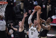 Milwaukee Bucks' Brook Lopez (11) and Atlanta Hawks' Onyeka Okongwu (17) and Danilo Gallinari (8) all go for a rebound during the first half of Game 4 of the NBA basketball Eastern Conference finals Tuesday, June 29, 2021, in Atlanta. (AP Photo/Brynn Anderson)
