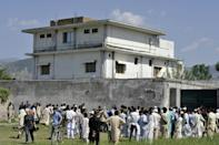 Journalists and local residents gather outside bin Laden's hideout after his death