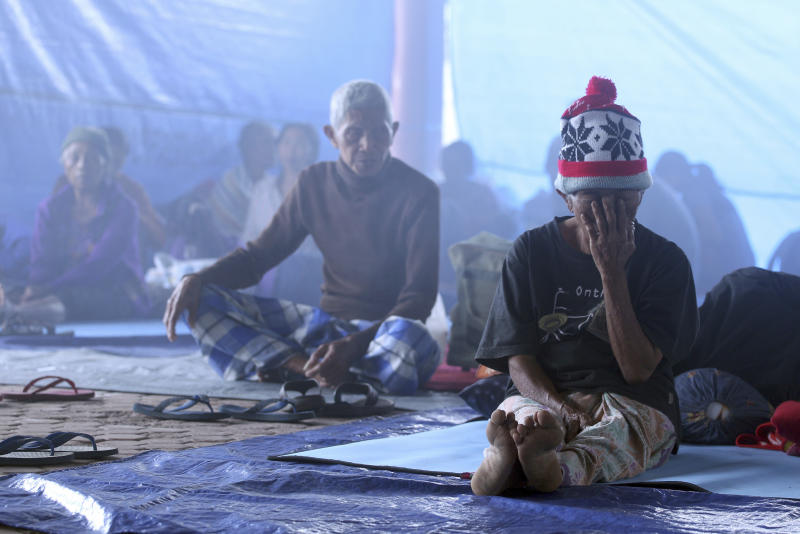 Villagers sit in a temporary shelter in Bali, Indonesia, Saturday, Sept. 23, 2017. Indonesian authorities raised the alert level for the Mount Agung volcano on the tourist island to the highest level, and more than 11,000 villagers left their homes around the mountain, officials said Friday. (AP Photo/Firdia Lisnawati)