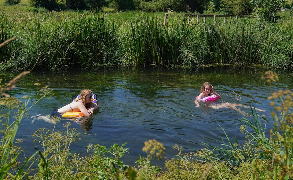 Two people use inflatables to make their way along the river Itchen near to Twyford in Hampshire (Andrew Matthews/PA) (PA Wire)