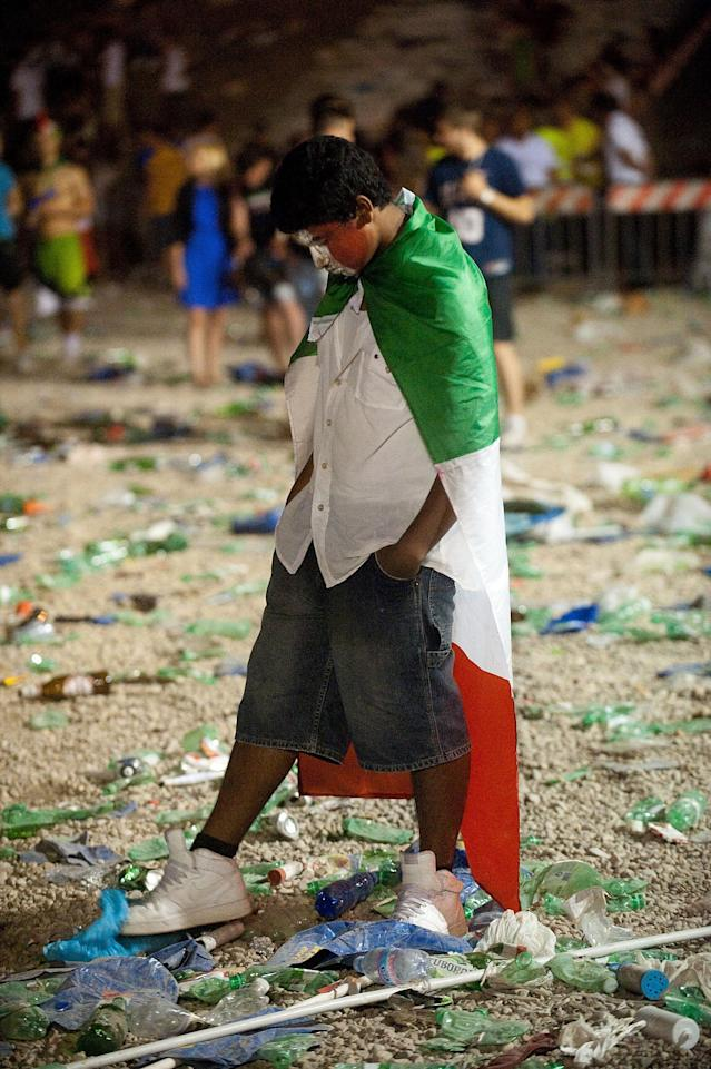 ROME, ITALY - JULY 01: A Italian fan covered with the national flag leaves after the UEFA EURO 2012 final match between Italy and Spain on a big screen at the Circus Maximo on July 1, 2012 in Rome, Italy. (Photo by Giorgio Cosulich/Getty Images)