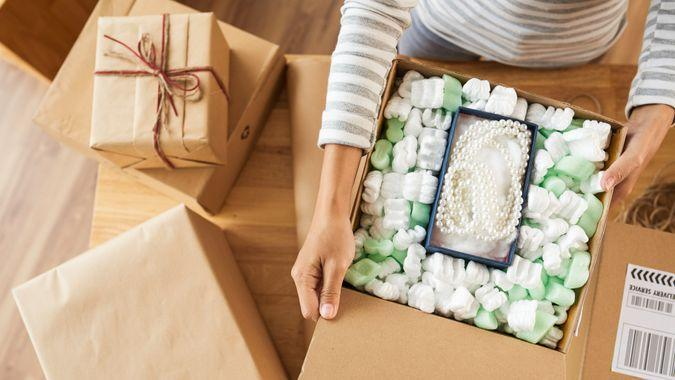 Woman opening many parcels she received, view from above, fees, America, money, payment, avoid fees, bills, debt