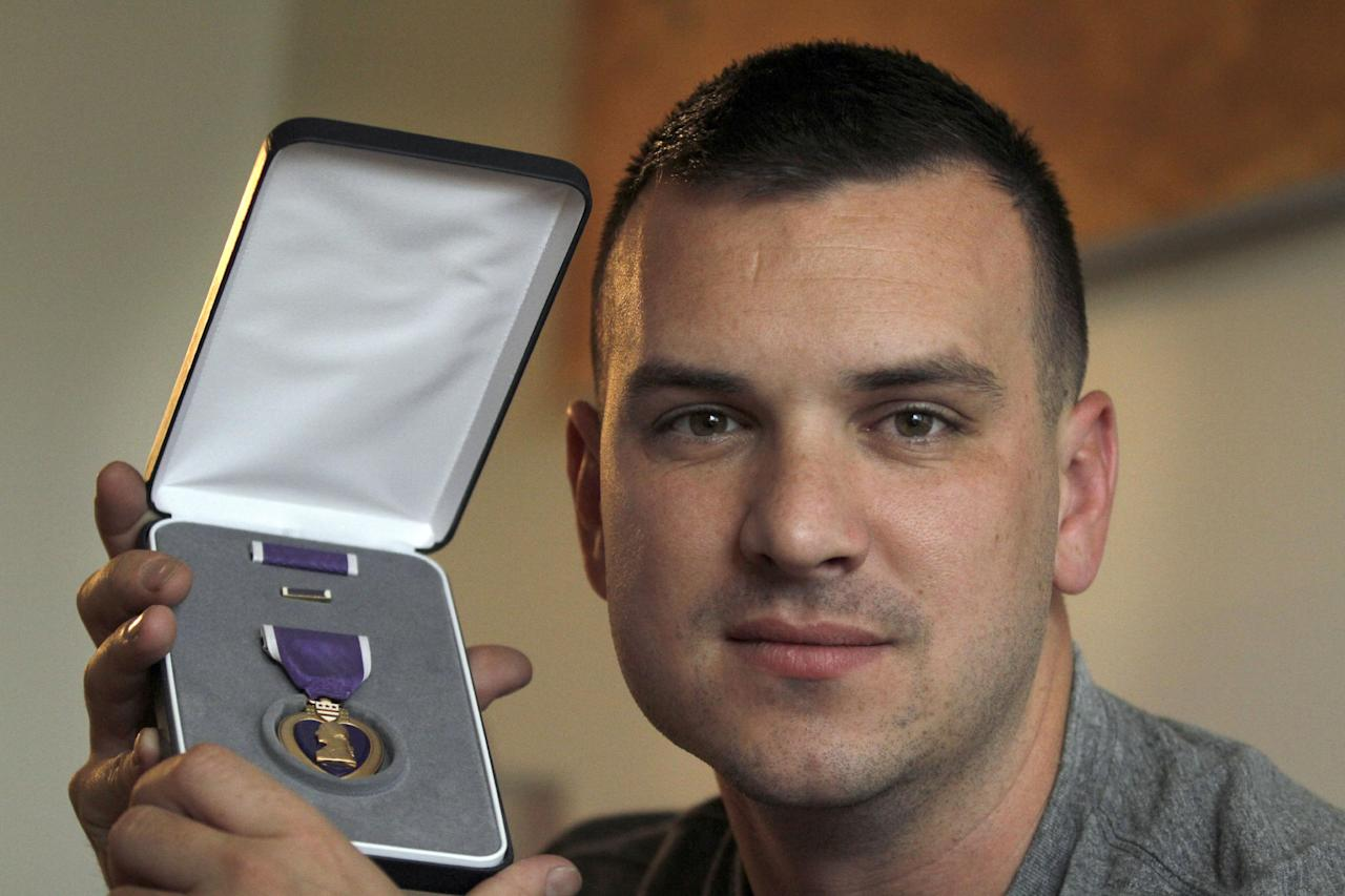 """In this Monday, Aug. 20, 2012 photo, Marine Sgt. Ron Strang holds his Purple Heart medal in the living room of his home in Jefferson Hills, Pa., just south of Pittsburgh. In 2008, the federal government created AFIRM, the Armed Forces Institute of Regenerative Medicine, a network of top hospitals and universities around the country, and gave $300 million in grants to spur new treatments using cell science and advanced plastic surgery. Strang is among those benefiting. The 28-year-old former Marine sergeant from Pittsburgh lost half of a thigh muscle to shrapnel, leaving too little to stabilize his gait. """"My knee would buckle and I'd fall over,"""" he said. Now, after an experimental cell treatment at the University of Pittsburgh Medical Center, """"I'm able to run a little bit"""" and play a light football game with friends, he said. """"It's been a huge improvement."""" (AP Photo/Keith Srakocic)"""