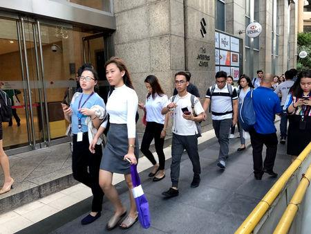 Employees walk outside after being evacuated from the office building after an earthquake in Makati City, Philippines, April 22, 2019. REUTERS/Martin Petty