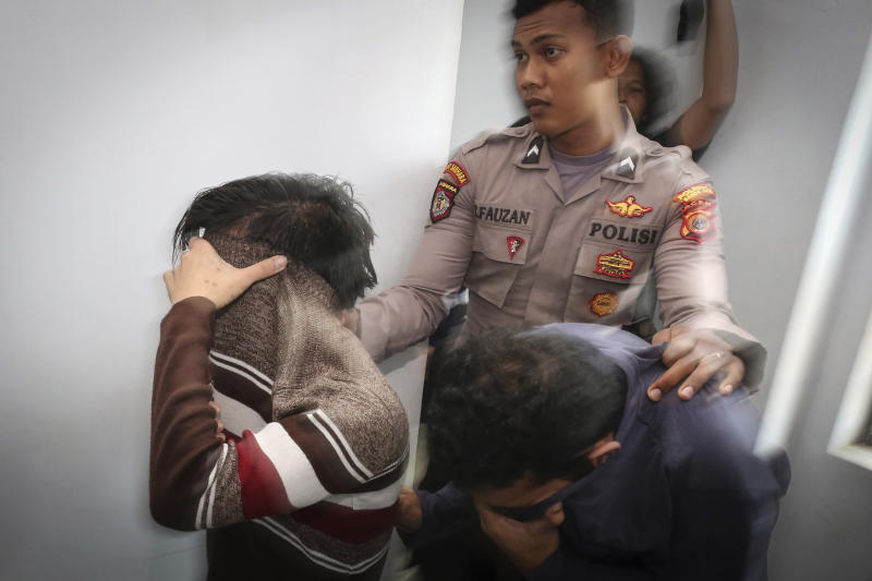 Police officer escorts two men accused of having gay sex into a holding cell to wait for the start of their trial at Shariah court in Banda Aceh, Indonesia, Wednesday, May 17, 2017. A Shariah court in Indonesia's conservative Aceh province has sentenced two gay men to public caning for the first time, further tarnishing the country's moderate image after a top Christian politician was imprisoned for blasphemy. (AP Photo/Heri Juanda)