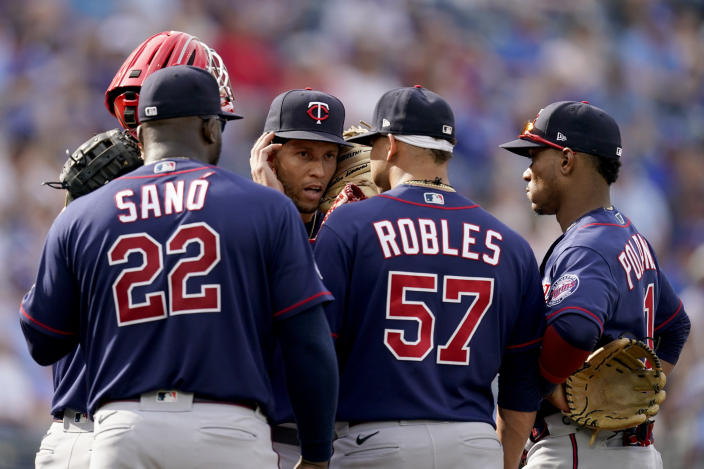 Minnesota Twins shortstop Andrelton Simmons, center, talks to teammates during a meeting on the mound during the ninth inning of a baseball game against the Kansas City Royals Saturday, June 5, 2021, in Kansas City, Mo. The Twins won 5-4. (AP Photo/Charlie Riedel)
