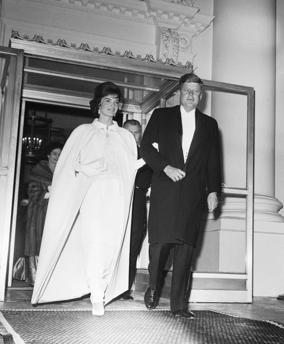 <p>Following a full day of inauguration events, the President and First Lady left the White House for the inaugural ball at the DC Armory. The President is seen in white tie, while Jacqueline Kennedy wears a white cape coat over her evening gown.</p>