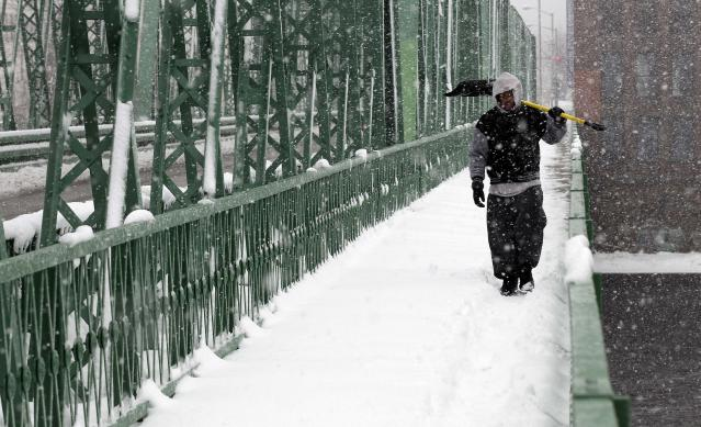 Jeffrey Colon carries his shovel across a bridge to help friends shovel out during a winter storm in Lawrence, Mass. Tuesday, March 19, 2013. Winter went out with a blast in the Northeast on Tuesday, snow and sleet delaying the start of school in some areas and making the morning commute an icy, slippery mess a day before spring starts. The nasty weather led some schools in upstate New York, Massachusetts and Connecticut to close, adding a few more snow days to school calendars. (AP Photo/Winslow Townson)