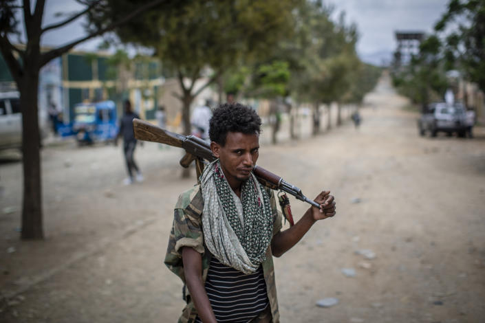 FILE - In this Friday, May 7, 2021 file photo, a fighter loyal to the Tigray People's Liberation Front (TPLF) walks along a street in the town of Hawzen, then-controlled by the group but later re-taken by government forces, in the Tigray region of northern Ethiopia. The Tigray forces that in late June 2021 have retaken key areas after fierce fighting have rejected the cease-fire and vowed to chase out Ethiopian government forces and those of neighboring Eritrea. (AP Photo/Ben Curtis, File)